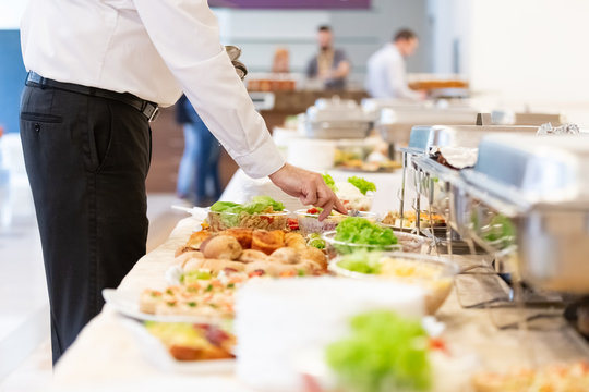 Close up of waiter hand preparing putting spoon in salad on buffet table.