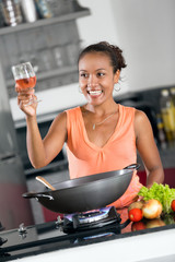 Young woman cooking for friends