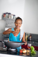 housewife in kitchen squeezes tomato in meal