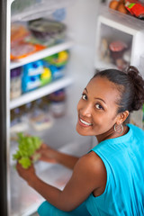 Young woman front open fridge