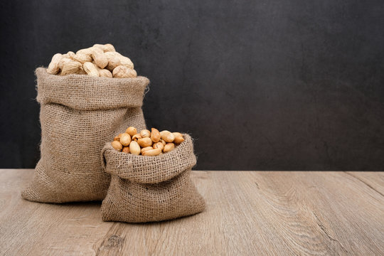 Peanuts in burlap bag and raw peanuts in nut shell, background is black wall for text
