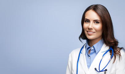 Happy smiling female young doctor in white uniform coat and stethoscope, isolated over grey background.