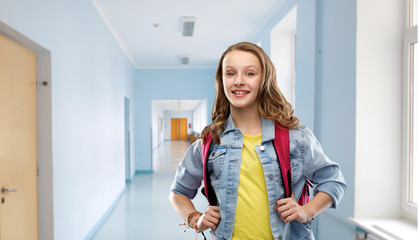 education and people concept - happy smiling teenage student girl with bag over school corridor background