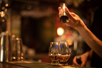 Bartender pouring whisky in a glass