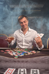 Handsome emotional man is playing poker sitting at the table in casino.