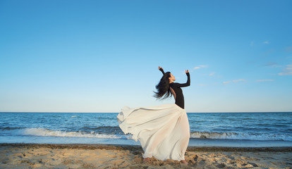 Classical dancer woman. Charming ballerina with windy hair in white chiffon skirt dancing by the sea background. Sun shines on her. Horizontal.