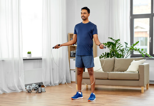 fitness, sport, exercising and healthy lifestyle concept - indian man skipping with jump rope at home