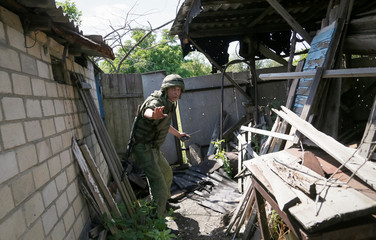 A serviceman of the separatist self-proclaimed Donetsk People's Republic gestures as he walks in a household, which locals said was damaged during recent shelling, outside rebel-held Horlivka