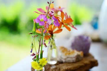 Amethyst and Citrine clusters on a wooden table, small vase of fresh flowers. Shot on macro lens in natural lighting. Bright colors, healing crystal clusters. Hippie natural healing and fresh herbs.