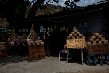 """Packages of 'casabe', a kind of a flatbread made of yucca, are displayed next to signs reading """"There is sale point"""" and """"Barters are made"""" near a road in Cupira"""