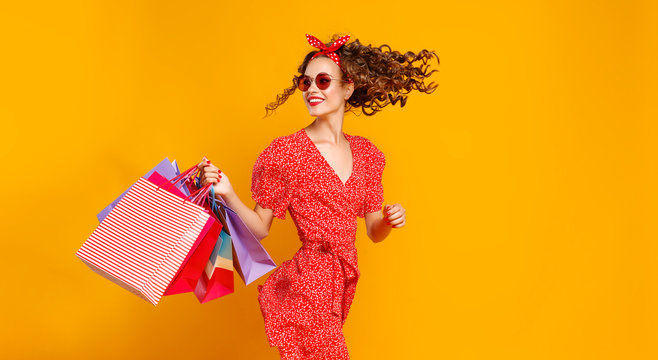 concept of shopping purchases and sales of happy young girl with packages  on yellow background