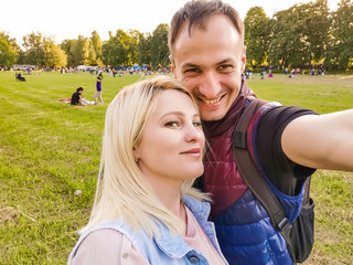 Closeup shot of young couple take selfie outdoor. Young man taking a photo with his girlfriend. Happpy smiling couple taking a selfie in a summer day