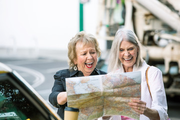 Two Women Checking a Map and Laughing