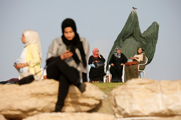 People enjoy themselves along the shore of the Mediterranean Sea during the Muslim holiday of Eid al-Fitr at a beach in Tel Aviv, Israel