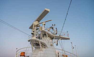 Navigation and radar equipment and antenna on the mast of cruise ship at dawn
