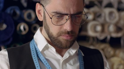 dae68395a1d2 0:09 Close up portrait of serious fashion tailor in glasses, choosing  material at work.
