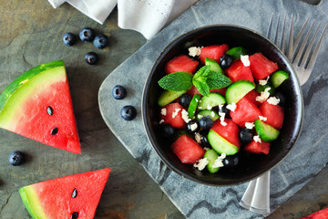 Watermelon salad with cucumber, blueberries and feta cheese. Overhead view close up scene on a dark background.
