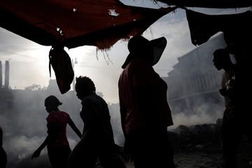 People walk past a pile of garbage in Port-au-Prince