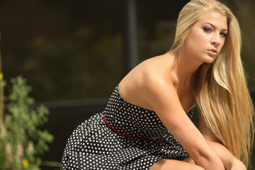 Beautiful blonde fashion model with dress in sitting the city