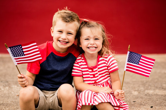 Cute siblings holding American flag while sitting on curb