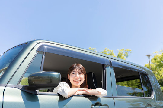 車窓から乗り出し外を眺める女性