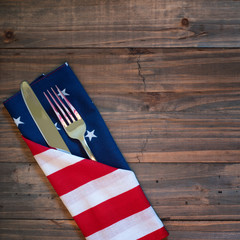 Fourth of July Table Place Setting with a fork, knife and flag napkin on rustic wood board background with room or space for copy, text, or your words.  It's a square photo with above view.