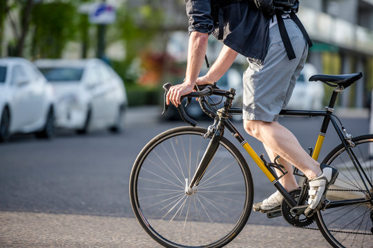 Cyclist in sneakers rides road bike presses the pedals to quickly cross the intersection