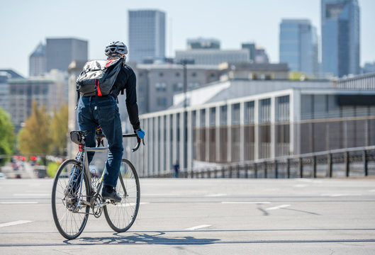 Man with backpack rides bike on the street of the city of Portland friendly for bike lovers