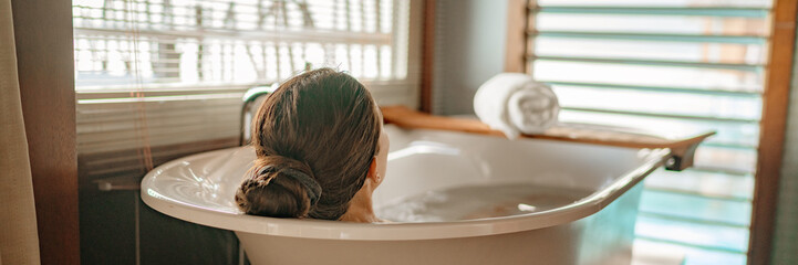 Acrylic Prints Relaxation Luxury bath woman relaxing in hot bathtub in hotel resort suite room enjoying pampering spa moment lifestyle banner panorama.