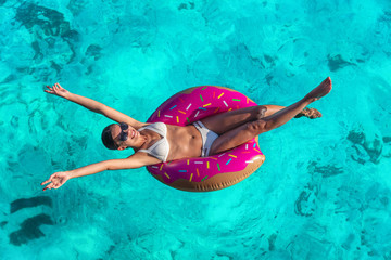 Summer vacation fun woman relaxing in donut swimming pool float with arms open in freedom and...