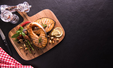Fototapete - Grilled salmon fish with seasoning and various vegetables on cutting board on black stone background