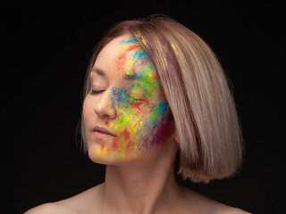 Studio portrait of young fashion model with bright colorful mix of paint.
