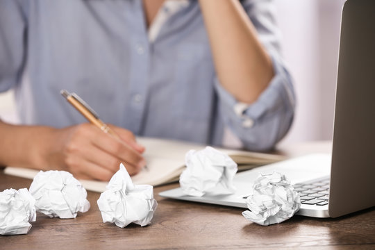 Woman working at table with crumpled paper, closeup. Generating idea