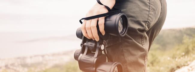 Unrecognizable woman with binoculars outdoor.