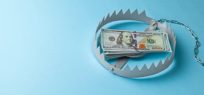 Trap with a stack of money. Dangerous risk for investment or deception in business. Blue background.