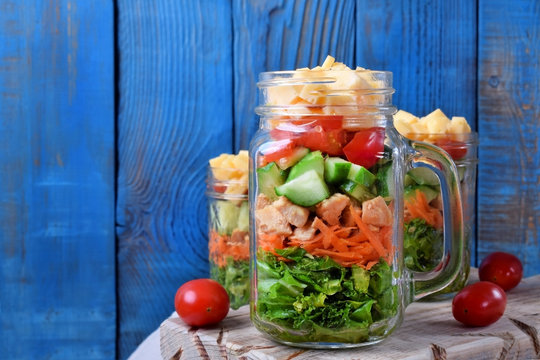 Layered salad with cheese, kale, carrot, chicken, cucumbers and cherry tomatoes in glass mason jars