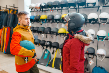 Couple trying on helmets for ski or snowboarding