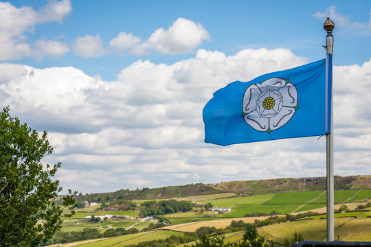 The White Rose of York flag blowing in the wind overlooking the Yorkshire Countryside