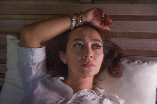 dramatic lifestyle portrait of attractive sad and depressed middle aged around 50s woman feeling upset alone on bed suffering depression and anxiety crisis