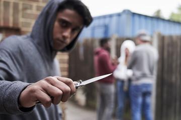 Teenage Boy In Urban Gang Pointing Knife Towards Camera