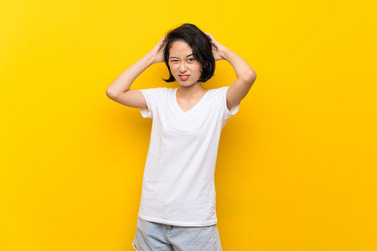 Asian young woman over isolated yellow wall frustrated and takes hands on head