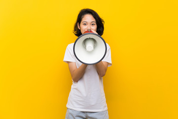Asian young woman over isolated yellow wall shouting through a megaphone Wall mural