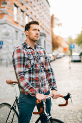 Young hipster man on fixie on street before sunset