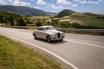 Classic car driving on winding road with nature in background Wall mural
