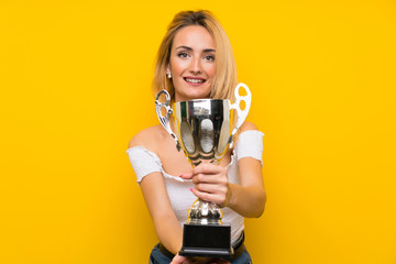 Young blonde woman over isolated yellow wall holding a trophy Wall mural