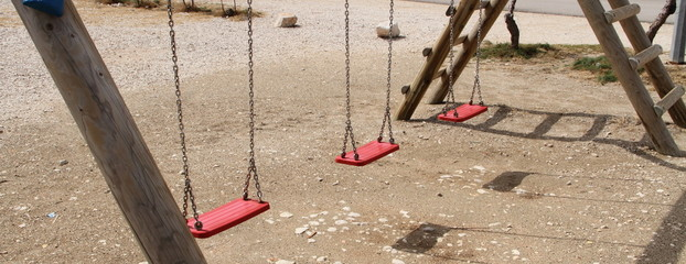 an empty swing on the playground