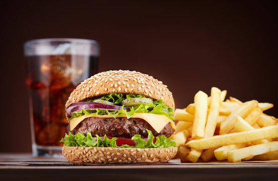 cheeseburger with french fries and glass of cola on wooden table