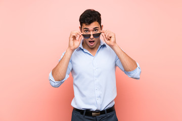 Handsome man over pink background with glasses and surprised