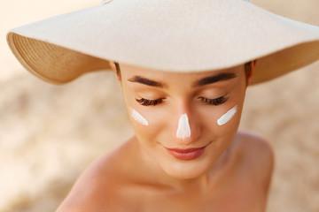Beauty Woman smile applying sun cream on face. Skin care. Body Sun protection. sunscreen. Female in hat smear moisturizing lotion on skin Wall mural