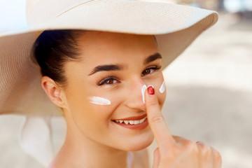 Beautiful Young woman with sun cream on face.  Female in hat applying  moisturizing lotion on skin.Skin care. Sun protection. Suntan Wall mural